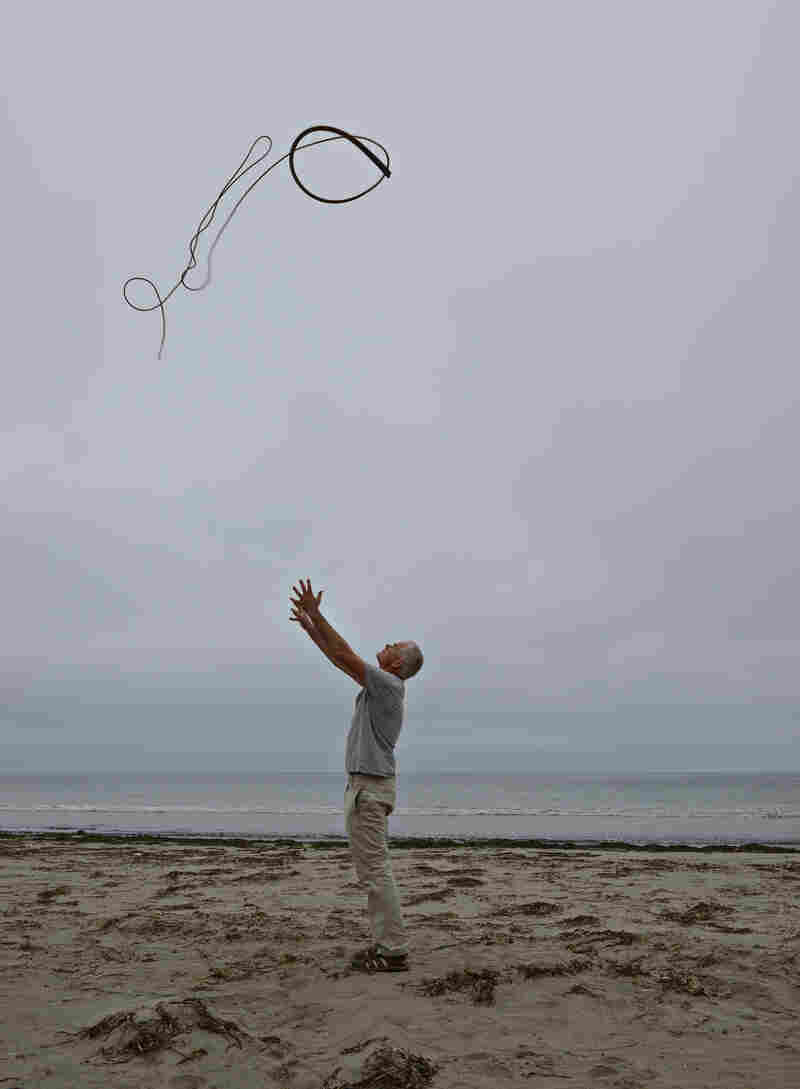 Andy Goldsworthy throws kelp into a gray, overcast sky in Drakes Beach, Calif. (July 14, 2013)
