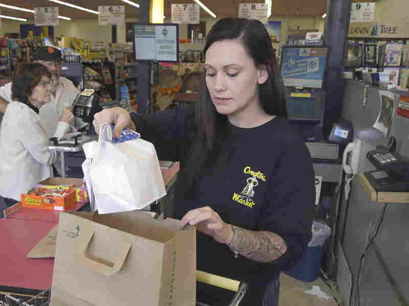 Checker Brittney Bounds bags groceries Tuesday in Sacramento, Calif. Gov. Jerry Brown signed an equal pay measure that lets female employees challenge pay discrimination based on the wages a company pays to male employees who do similar work.