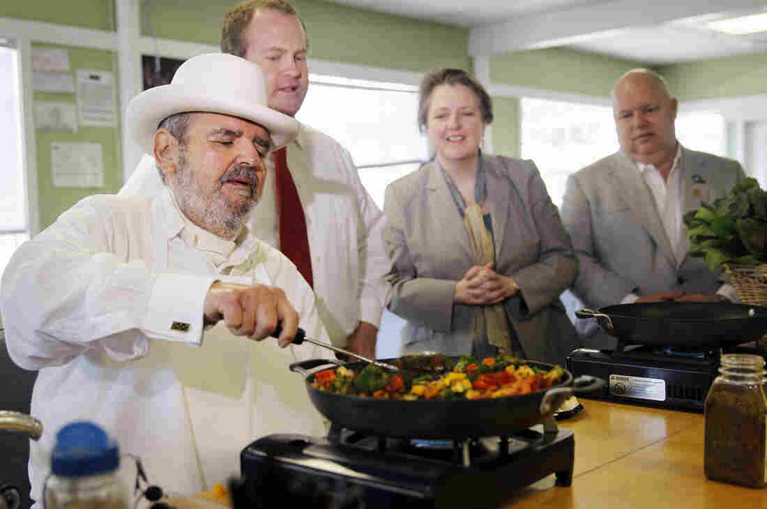 Paul Prudhomme leads a cooking demonstration after then-Agriculture Secretary Kathleen Merrigan (second from right) discussed food hubs in New Orleans in 2013.