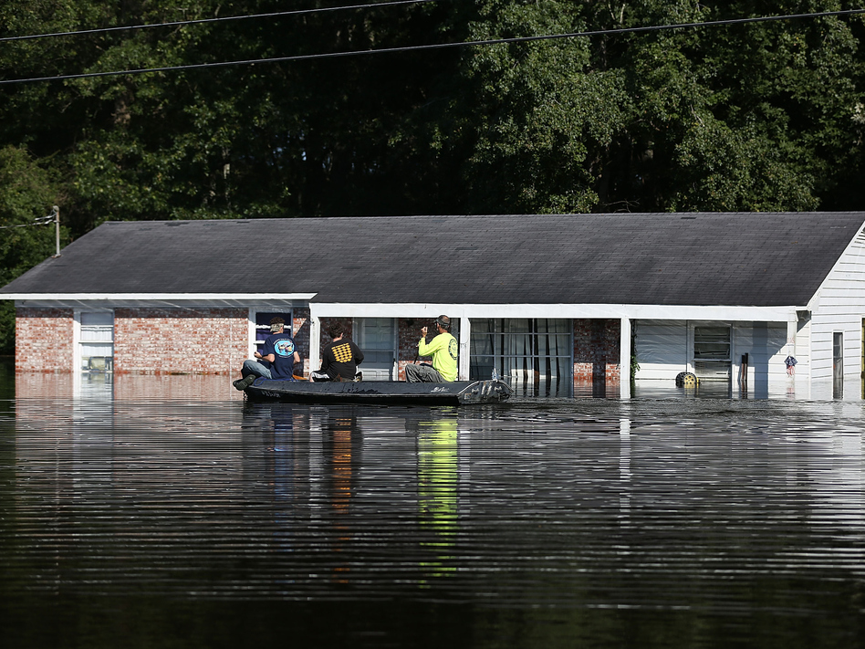 People paddle past a flooded house as water that breached dams upstream continues to reach the eastern part of the state on October 8, 2015 in Andrews, S.C. Many dams in the state — and across the country — are in need of repair.