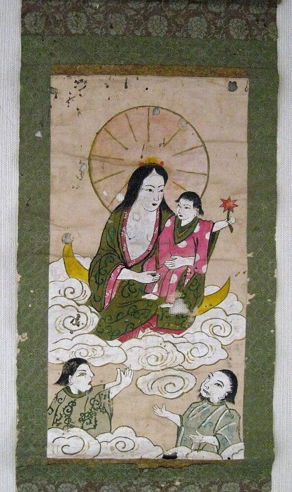 A Japanese hidden Christian wall scroll depicts the Virgin Mary holding the young Jesus Christ, with two saints looking on. To avoid persecution, hidden Christians disguised their religion under a veneer of Buddhist and Shinto imagery.