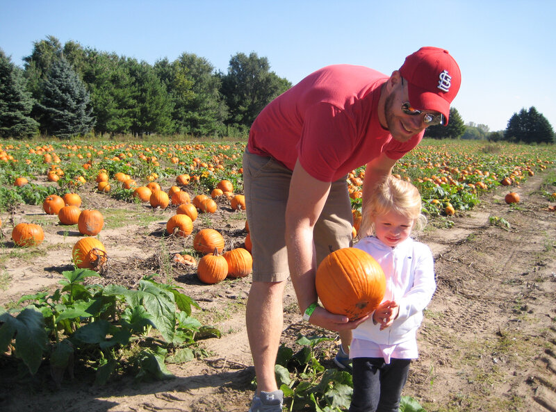 Kevin Coppinger took his nearly 3-year-old daughter, Mae, to choose a pumpkin at Waldoch Farm. The farm added a corn maze about five years ago. Owner Doug Joyer says adding such attractions has allowed him to live solely off income from the farm. (Kaomi Goetz/NPR)