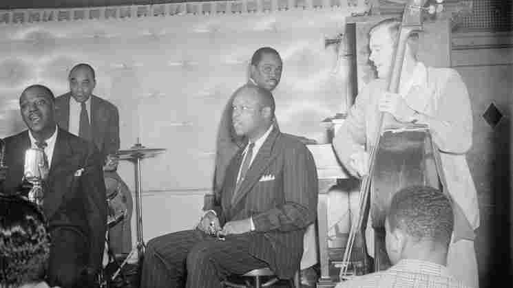 Sammy Price (background, seated at piano) with Sidney De Paris, Freddie Moore, Eddie Barefield and Charlie Traeger.
