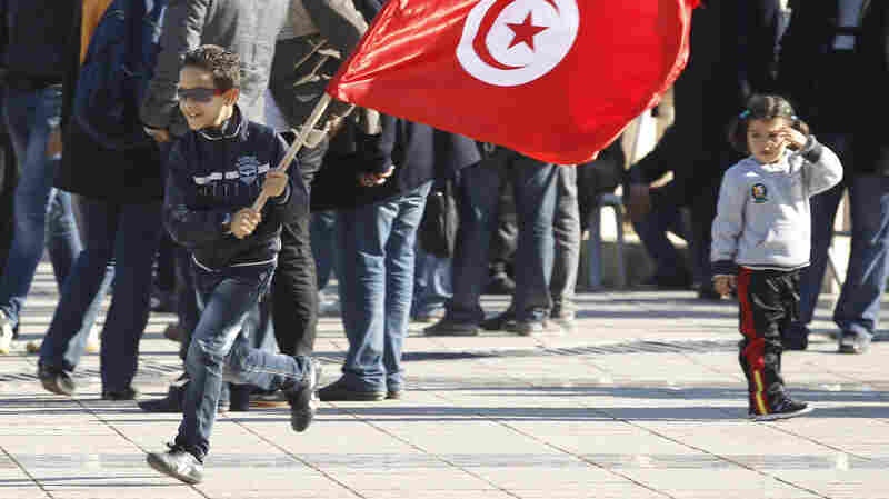 """December 2013: A Tunisian boy waves a flag as he runs at a rally in Tunis, marking the third anniversary of Tunisia's revolution. A prominent member of the group that's credited with averting civil war in the country says the group acted """"to give hope to young people."""""""