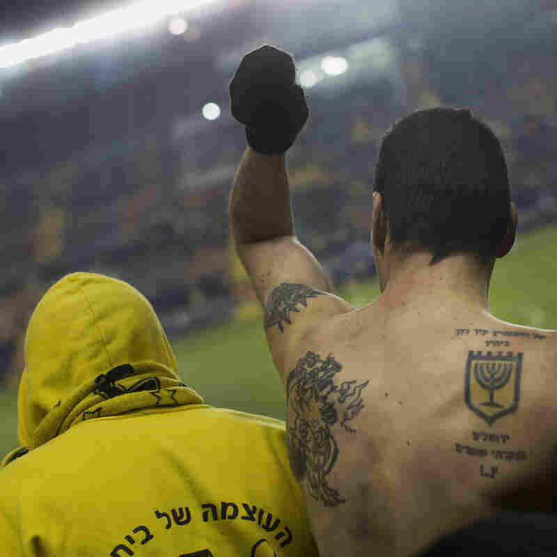 "Beitar Jerusalem fans watch a State Cup soccer match against Maccabi Umm al-Fahm F.C. at the Teddy Stadium in Jerusalem. The right tattoo shows the Beitar Jerusalem logo and reads, ""I have set watchmen on your walls, Jerusalem; they shall never hold their peace day nor night."""