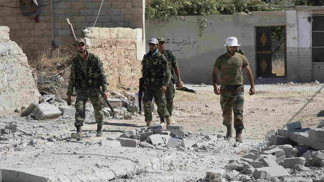 A photo from Sunday shows Syrian soldiers in Achan, Hama province. Bolstered by Russian jet strikes, Syria's army and its allies have reportedly pushed out insurgents in some parts of the central province.