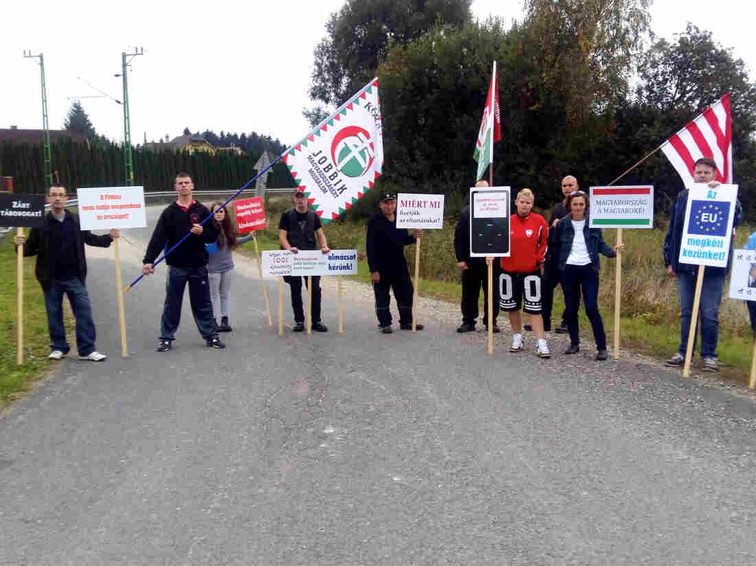 About 20 people wave anti-immigrant placards and flags at a Jobbik rally last Tuesday in Szentgotthárd, a rural factory town near Hungary's border with Austria.