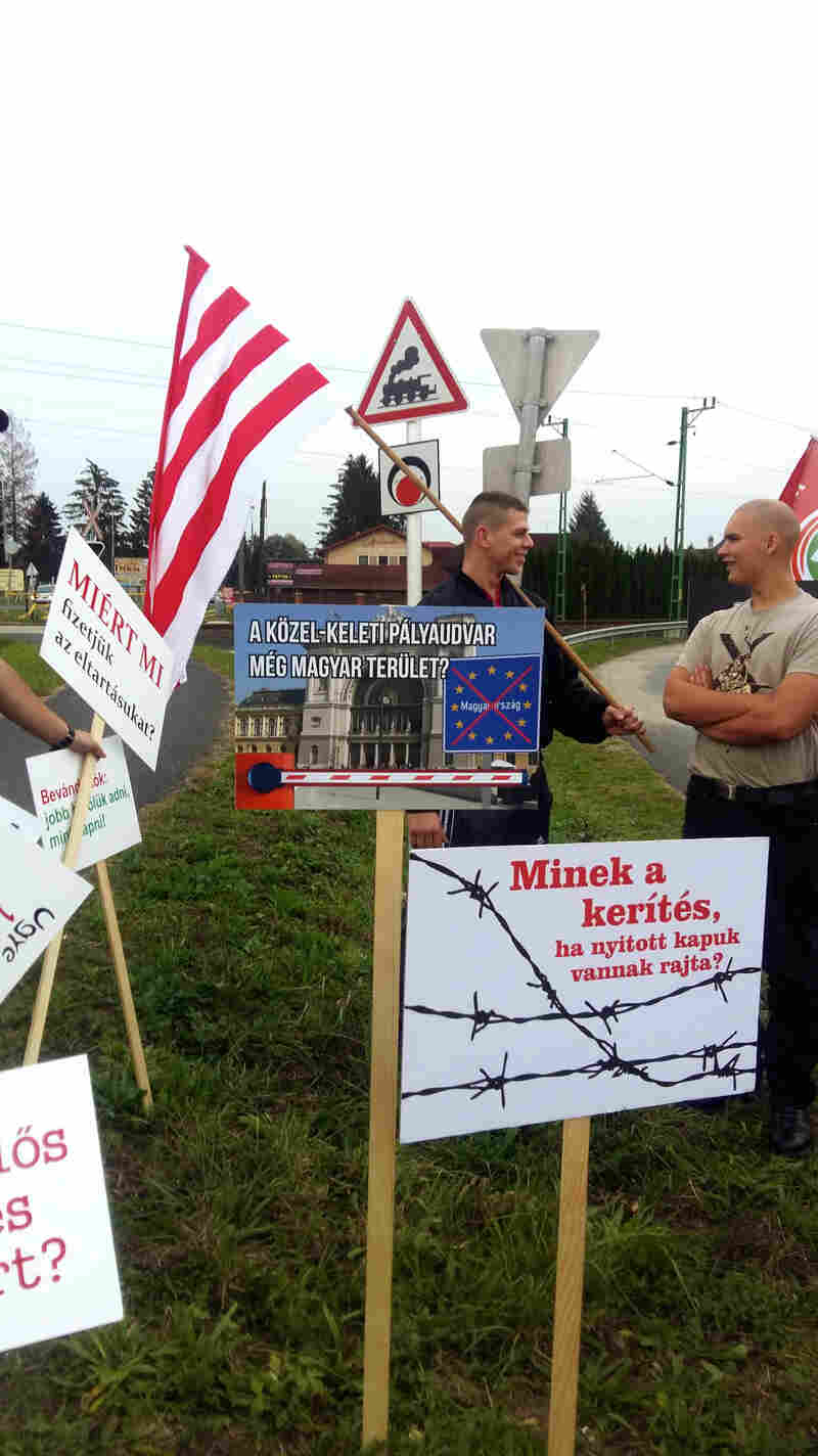 "Anti-immigrant placards at a Jobbik rally read ""Why have a fence if the gates on it are open?"" (lower right) and ""Is this a Middle Eastern train station or is it Hungarian?"" (center)."