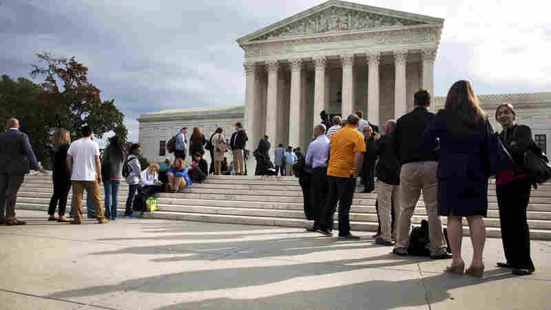 People line up outside the Supreme Court Tuesday ahead of arguments in Montgomery v. Louisiana, a case looking at whether a 2012 high court decision regarding mandatory life sentences should apply retroactively.