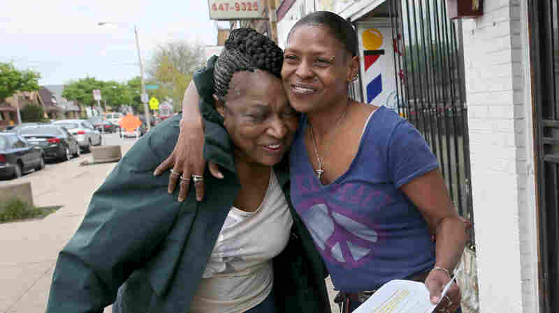 """Sarah White (right) hugs """"Mother"""" Martha Freeman, known as the change-maker or a violence-interrupter, in the Garden Homes Park neighborhood of Milwaukee, Wis."""