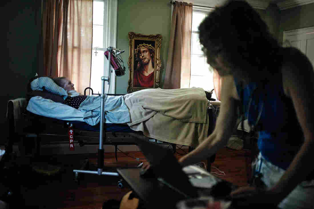 Patricia Gillihan, 71, lies in her home hospital bed while Miller checks her medical records.