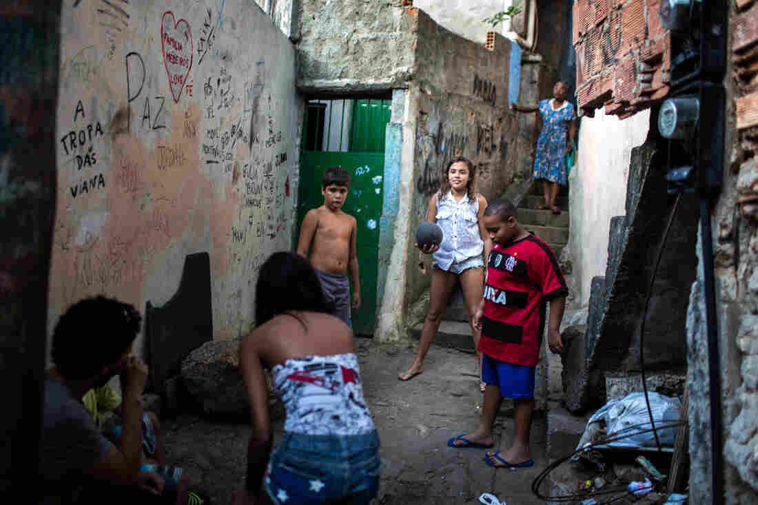Lala (center) and Milena (back to camera) play a pickup game of soccer in their neighborhood, the Rocinha favela, a shantytown in Rio de Janeiro.