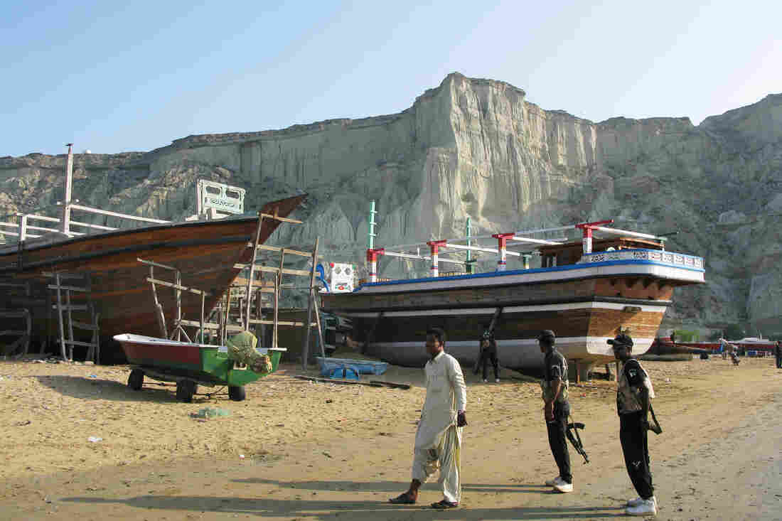 Boat-building on the beach at Gwadar, watched over by anti-terrorism commandos. Separatists carry out periodic attacks in Balochistan, the province in southwestern Pakistan.