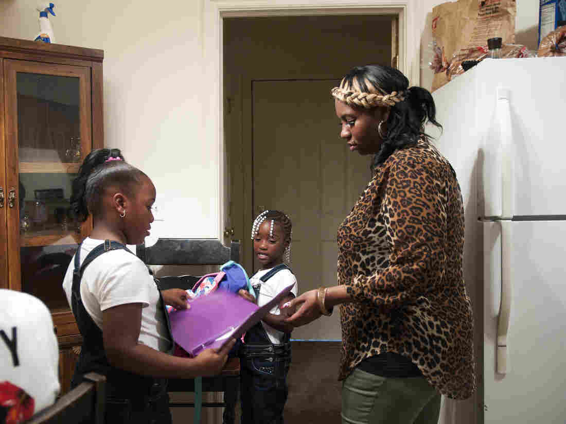 Rachel Jenkins welcomes her daughters Kyonna Jenkins (left) and Ti'yonna Hill home from school in Boley, Okla. Rachel injured her shoulder while working as a nursing assistant and was originally denied benefits because she reported the incident three hours too late.