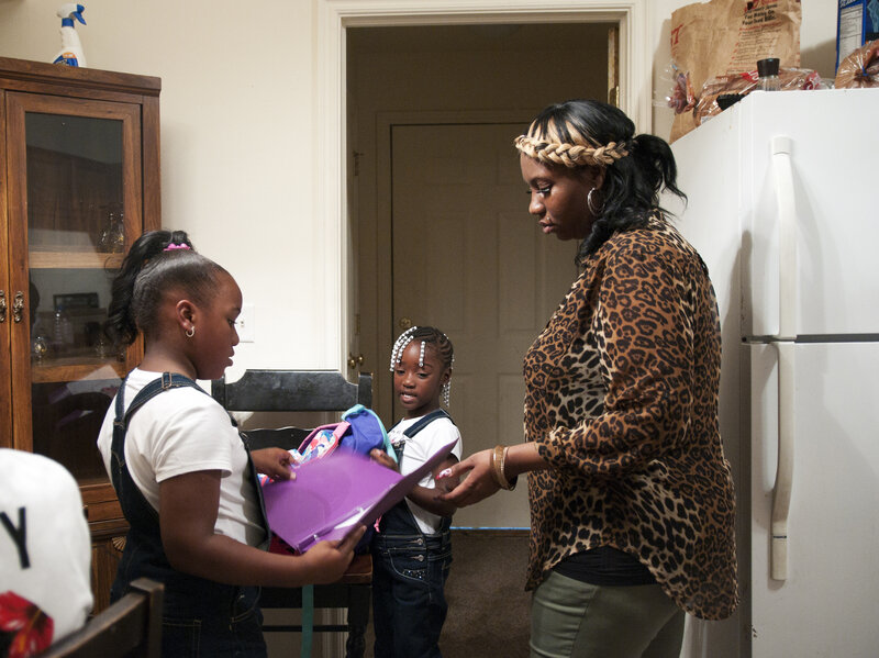 Rachel Jenkins welcomes home her daughters Kyonna Jenkins, (left), and Ti'yonna Hill from school in Boley, Okla. Rachel injured her shoulder while working as a nursing assistant and was originally denied workers' comp benefits because she reported the incident three hours too late.