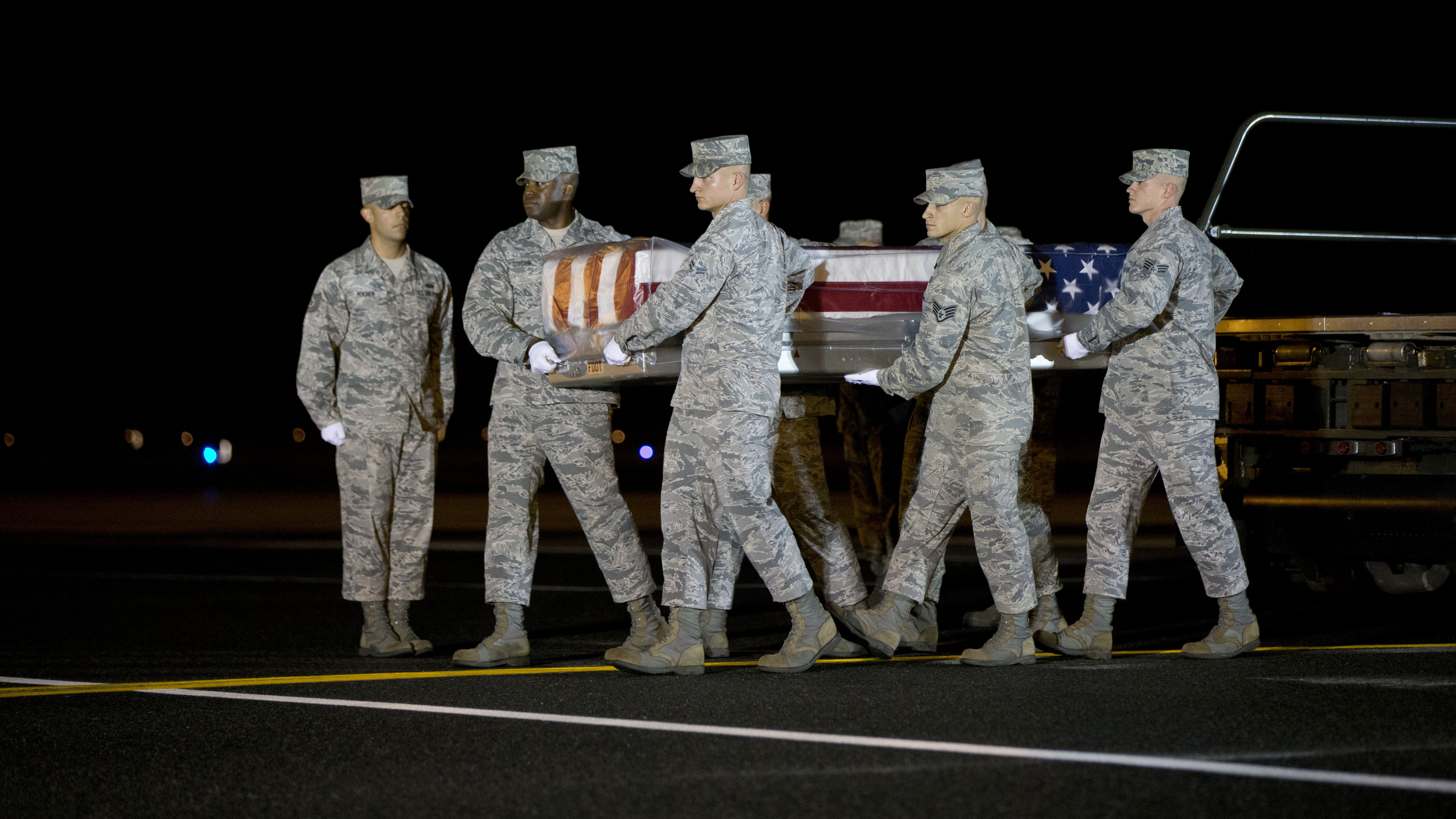 An Air Force team carries the transfer case with the remains of Maj. Phyllis J. Pelky at Dover Air Force Base, Del., on Tuesday. Pelky, 45, was killed two days earlier in a helicopter crash in Afghanistan. Though the U.S. formally ended its combat role in Afghanistan last year, 25 Americans, including military personnel and civilians, have been killed there this year.