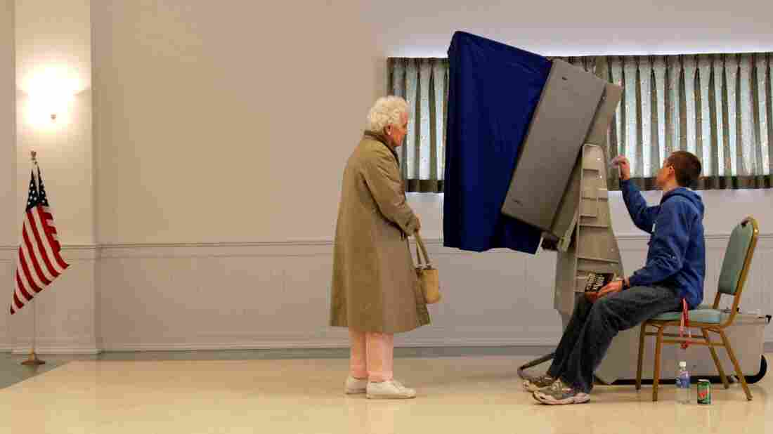 An election worker resets a voting machine as a voter waits in 2008. Many of the country's machines were replaced after the 2000 election, but are now reaching the end of their useful lives.