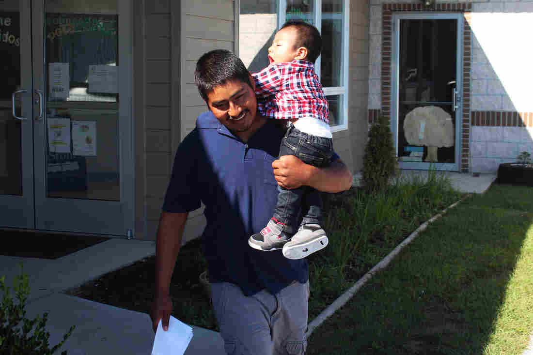 "Martinez carries his toddler son, Richard, from the Head Start school building. The family spends about half the year in Florida, where there's work through the winter. That's the closest approximation of ""home."" The rest of the year, the children move from one school or preschool to another."