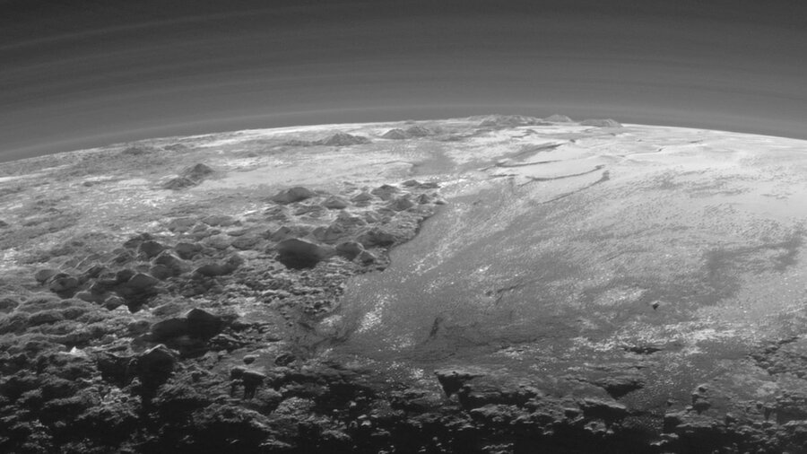 This image of Pluto, taken just 11,000 miles from the surface, reveals mountains of solid ice, against a hazy atmosphere. (NASA/JHUAPL/SwRI)