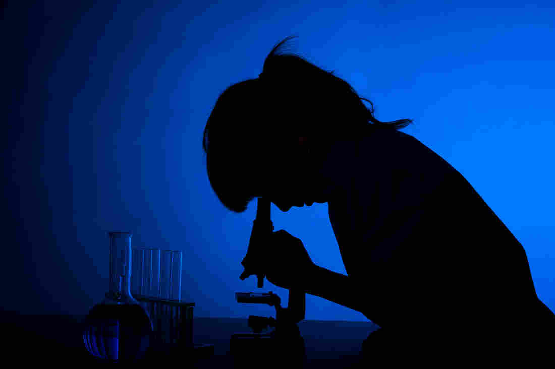 Silhouette of a woman scientist at the microscope.