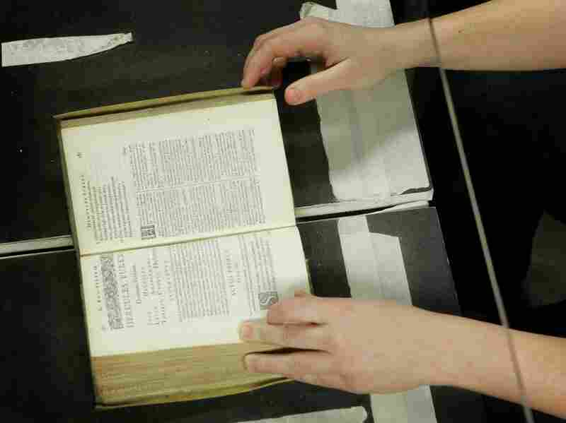 A librarian working with the Google Books project in Ann Arbor, Mich., helps a giant desktop machine scan a rare, centuries-old Bible in 2008.