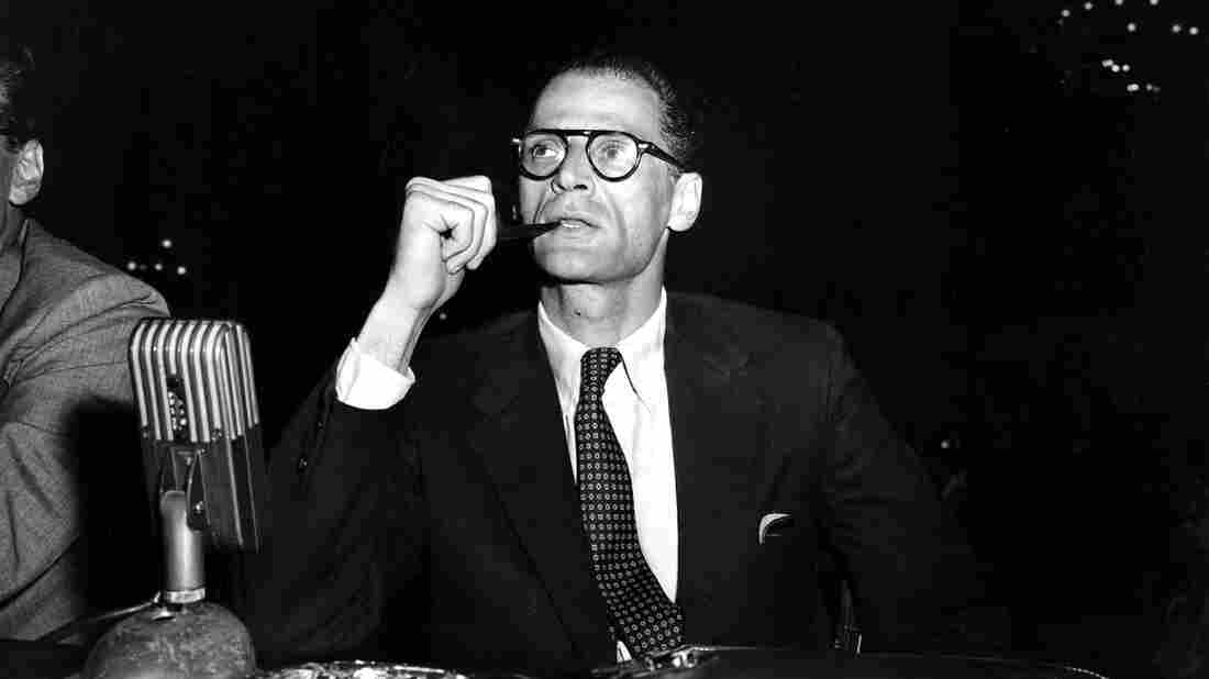 Arthur Miller smokes his pipe at the witness table prior to testifying at a hearing before the House Un-American Activities Committee in Washington, D.C., on June 21, 1956.
