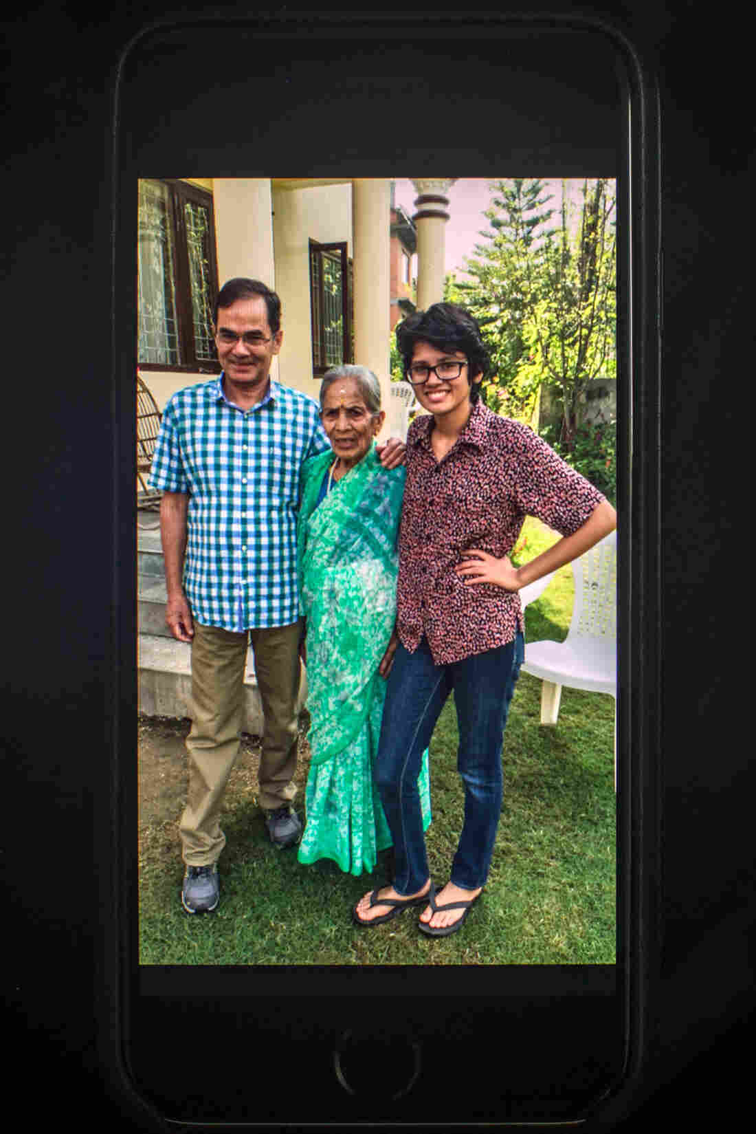 In this family photo, Prakriti Kandel poses with her grandmother and father in their garden.