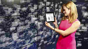 A woman holds up a tablet to showcase data analytics conducted by IBM's Watson technology.