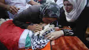 A relative kisses the body of Iyad Awawdeh, 26, during his funeral in the West Bank on Saturday. Awawdeh was killed after he stabbed an Israeli soldier.