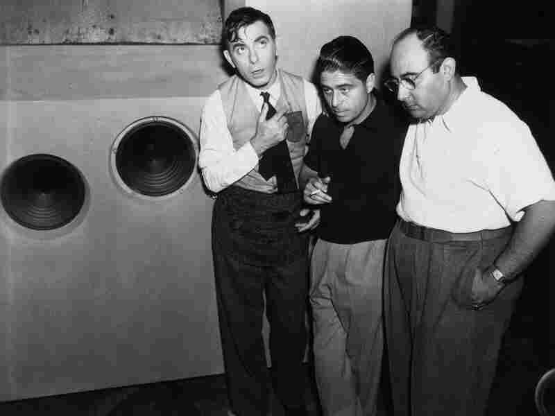 Alfred Newman stands between actor Eddie Cantor (left) and director Norman Taurog, listening to a playback on the set of Strike Me Pink, circa 1935.
