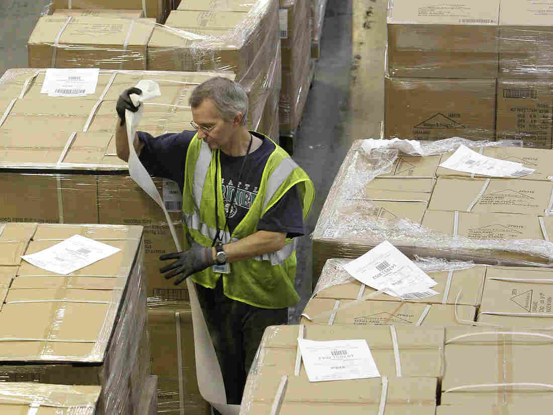 A dock clerk labels boxes as they arrive at an Amazon.com fulfillment center in Phoenix.
