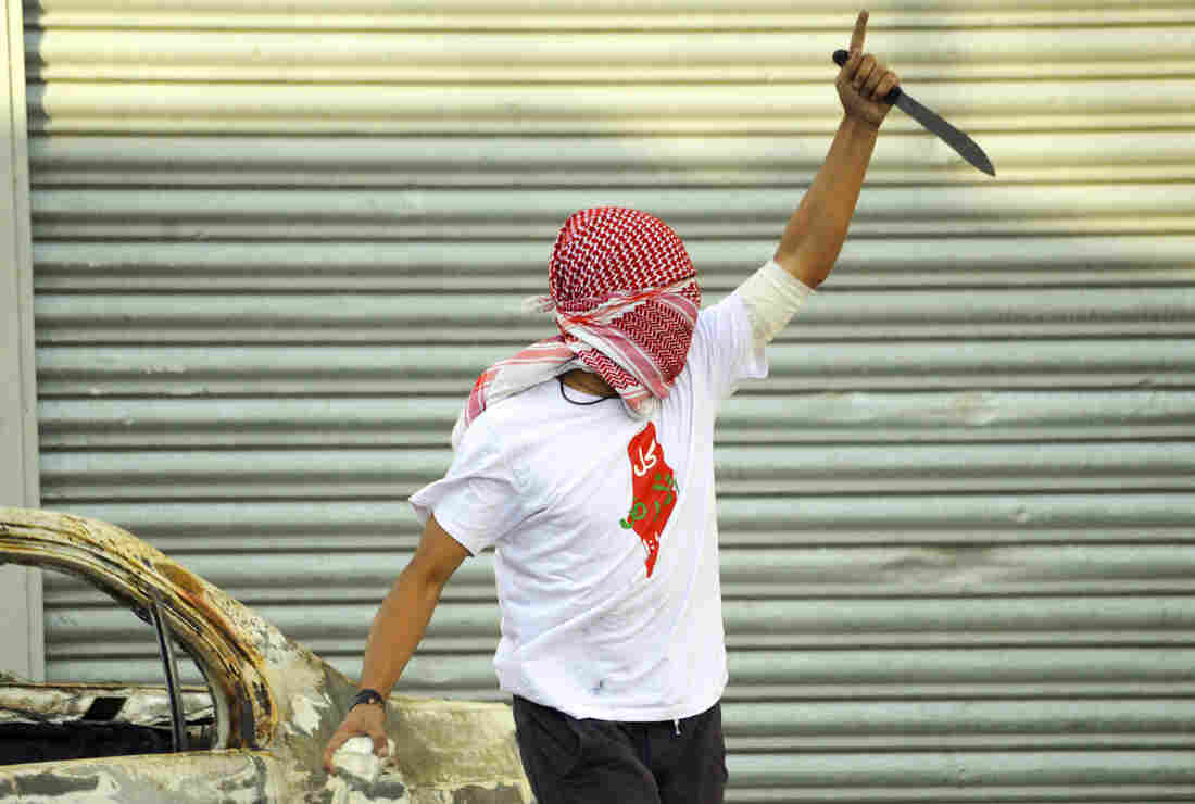 A Palestinian raises a knife during clashes with Israeli police in the Shuafat refugee camp in Jerusalem on Oct. 9. After a series of Palestinian stabbing attacks, some Israeli stores have removed knives from their shelves.