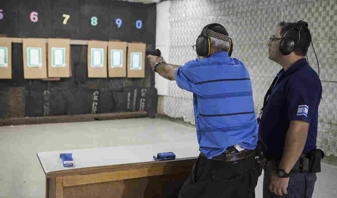 An Israeli fires his weapon at a shooting range near the West Bank Jewish settlement of Givat Zeev on Oct. 11. Gun store owners in Israel say sales have been rising in response to the recent violence.