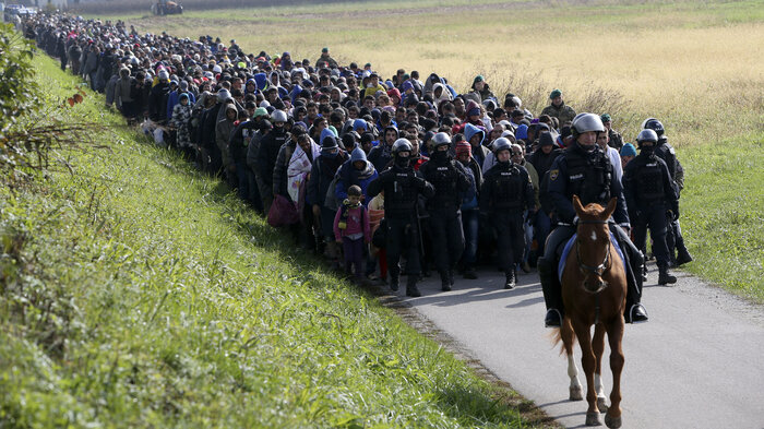 A policeman on horseback and other officers lead a group of refugees and migrants near Dobova, Slovenia, Tuesday. Slovenia's parliament is expected to approve a measure to have the army help police guard the border with Croatia.