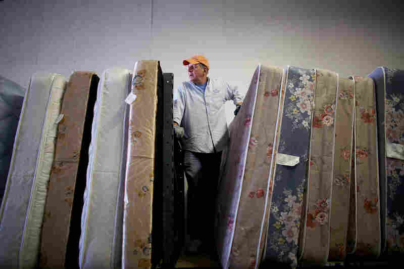 Volunteers from Epworth Furniture Ministry prepare donated mattresses for distribution in Perrysburg, Ohio. A tight-knit group of volunteers and assistance agencies in the Toledo area help incoming refugees and local families in need.