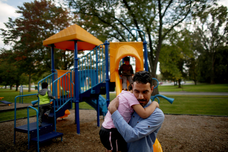 Omar holds his daughter, Taiba, at the playground near the family's new home in Toledo. (David Gilkey/NPR)