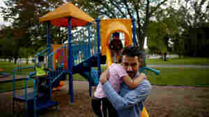 Omar holds his daughter, Taiba, at the playground near the family's new home in Toledo.