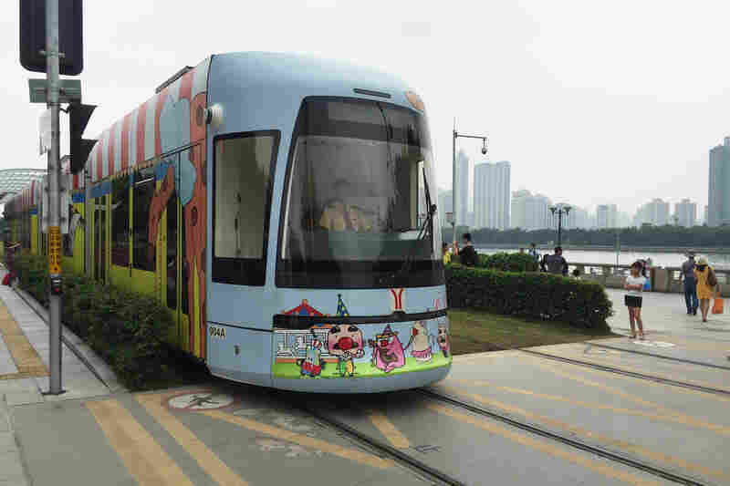 A circus-themed streetcar approaches a pedestrian crosswalk in Guangzhou, China.