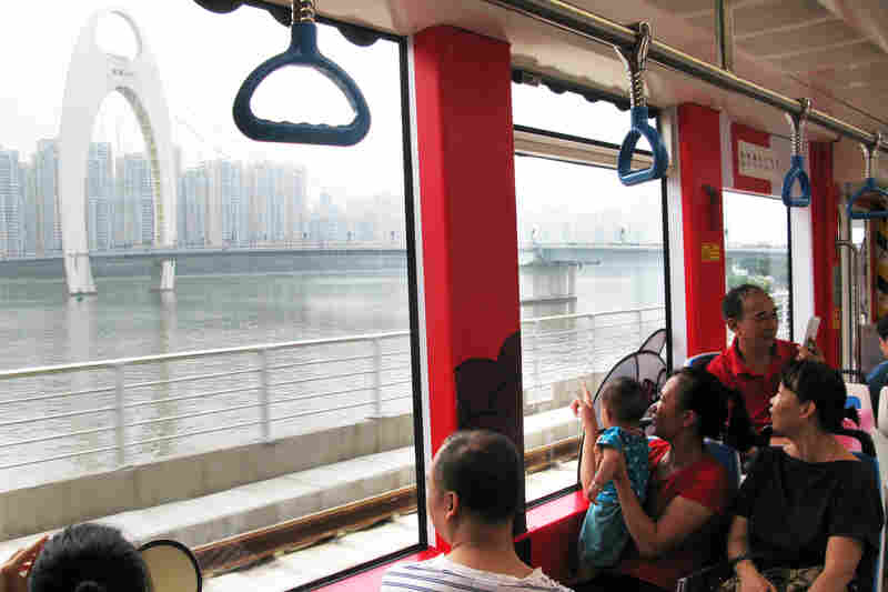 Streetcar passengers look out the window at Guangzhou's Pearl River.