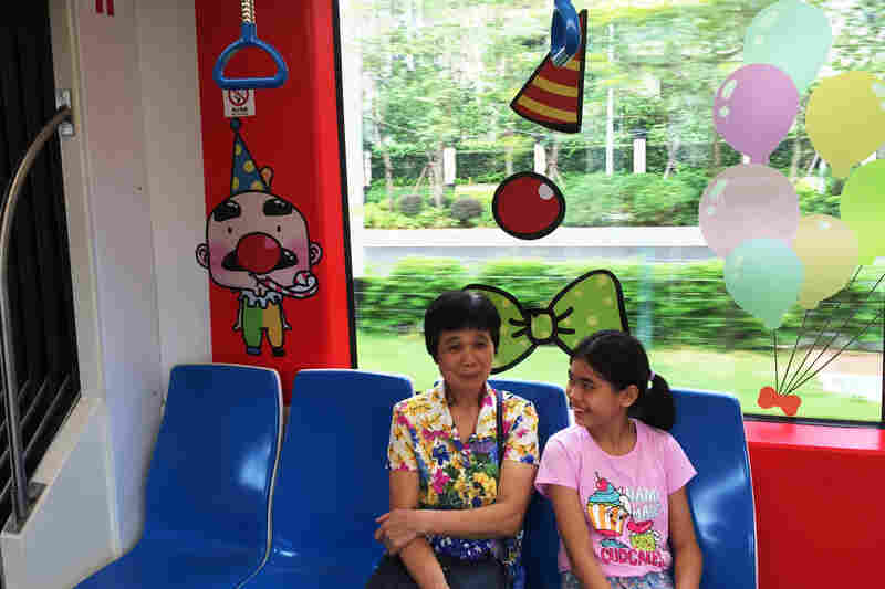 A mix of locals and tourists snap pictures and watch scenery as the streetcar makes its way through Guangzhou's up-and-coming Haizhu district. This streetcar has a kid-friendly theme with clowns and circus animals.