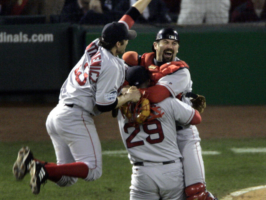 Boston Red Sox's Doug Mientkiewicz, left, and catcher Jason Varitek, right, jump into Keith Foulke's arms after the Red Sox defeated the St. Louis Caridnals 3-0 in Game 4 to win the 2004 World Series. (Sue Ogrocki/AP)