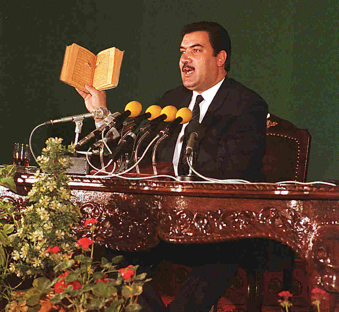 Afghan leader Najibullah displays a Quran with a bullet hole at a news conference in Kabul in 1987. He said a rebel fighter had shot the hole in the Muslim holy book. Despite Russia's support, Najibullah was toppled in 1992 and later killed by the Taliban.
