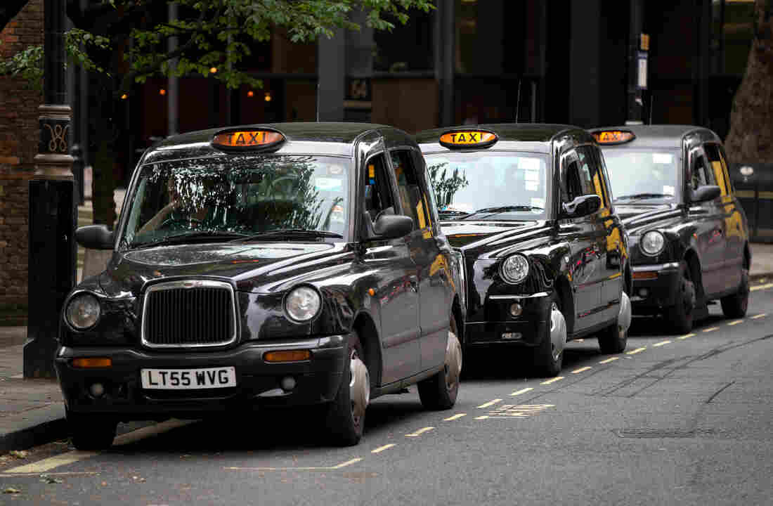 Taxis wait in London in June 2014. By law, the drivers of London's black cabs must memorize all of the city's streets, a process that takes years of study. The taxi drivers are opposed to Uber and drivers using a GPS, but the High Court ruled in favor of Uber last week.