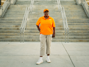 "Qumotria Kennedy, 36, stands at the baseball field in downtown Biloxi where she worked as a contract maintenance employee. She's a plaintiff in an ACLU lawsuit accusing the city of operating an illegal ""debtors' prison."""