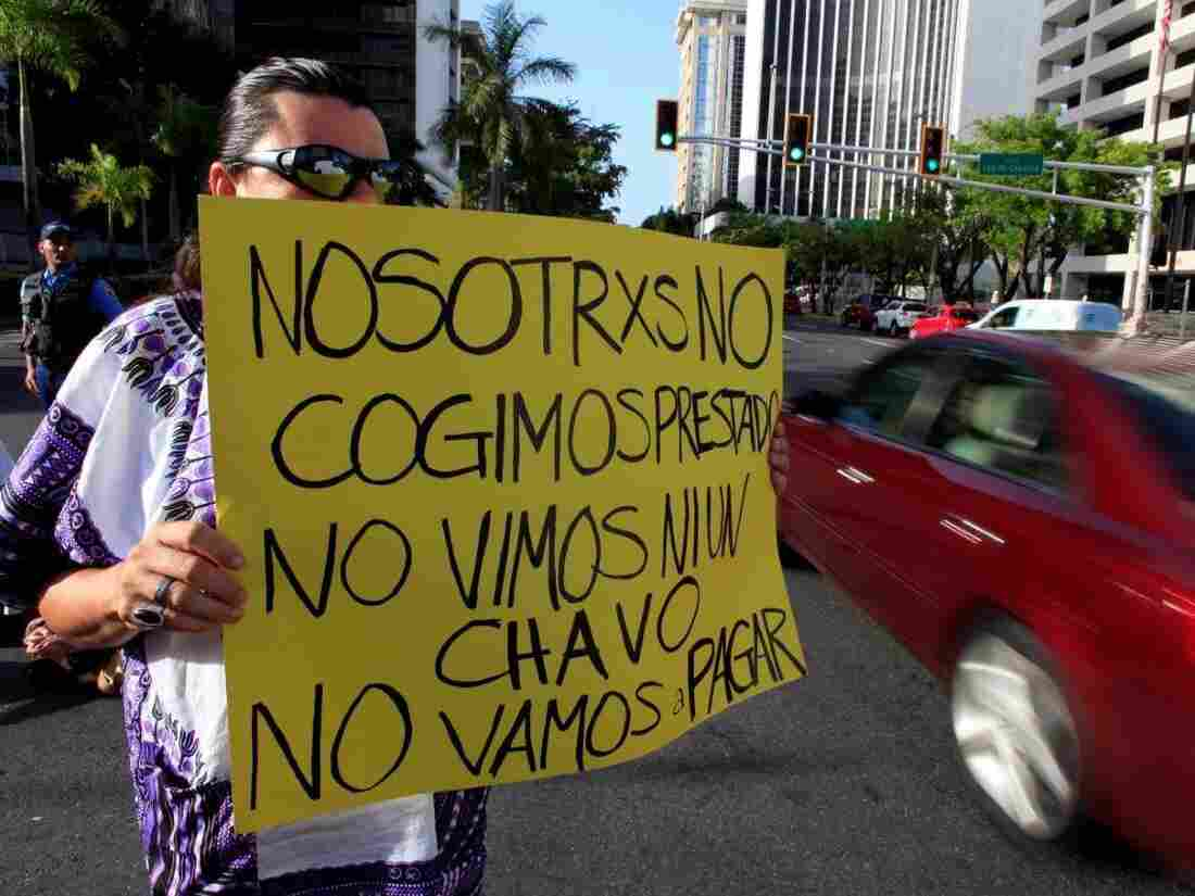 "A demonstrator protesting the negotiations with Puerto Rico's creditors in July holds up a sign that reads,  ""We didn't take out a loan. We didn't see a dime. We're not going to pay."""