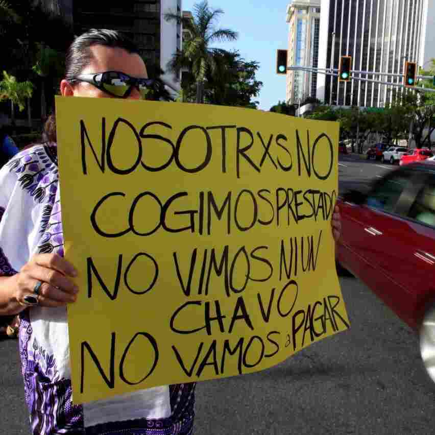 """A demonstrator protesting the negotiations with Puerto Rico's creditors in July holds up a sign that reads,  """"We didn't take out a loan. We didn't see a dime. We're not going to pay."""""""