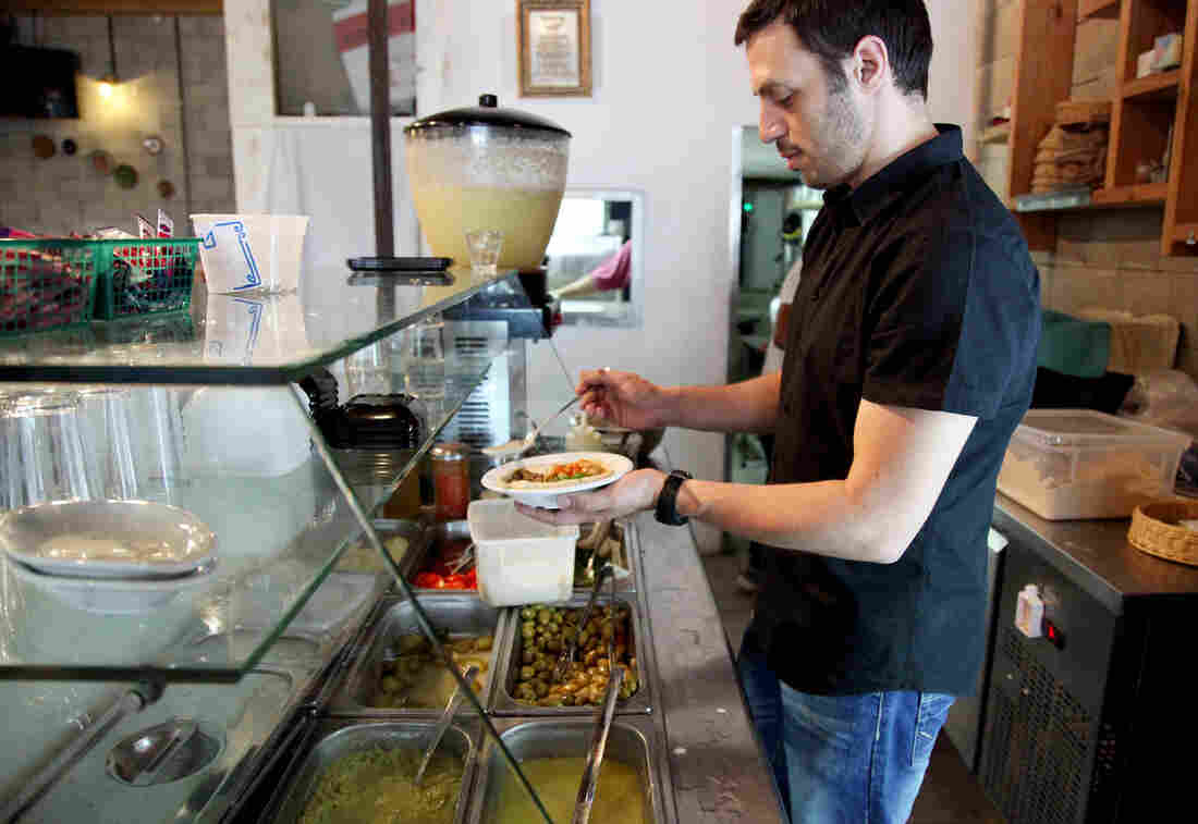 "Kobi Tzafrir serves hummus at the Humus Bar, his restaurant north of Tel Aviv, Israel. ""If you eat a good hummus, you will feel love from the person who made it,"" he tells The Salt. ""You don't want to stab him."""