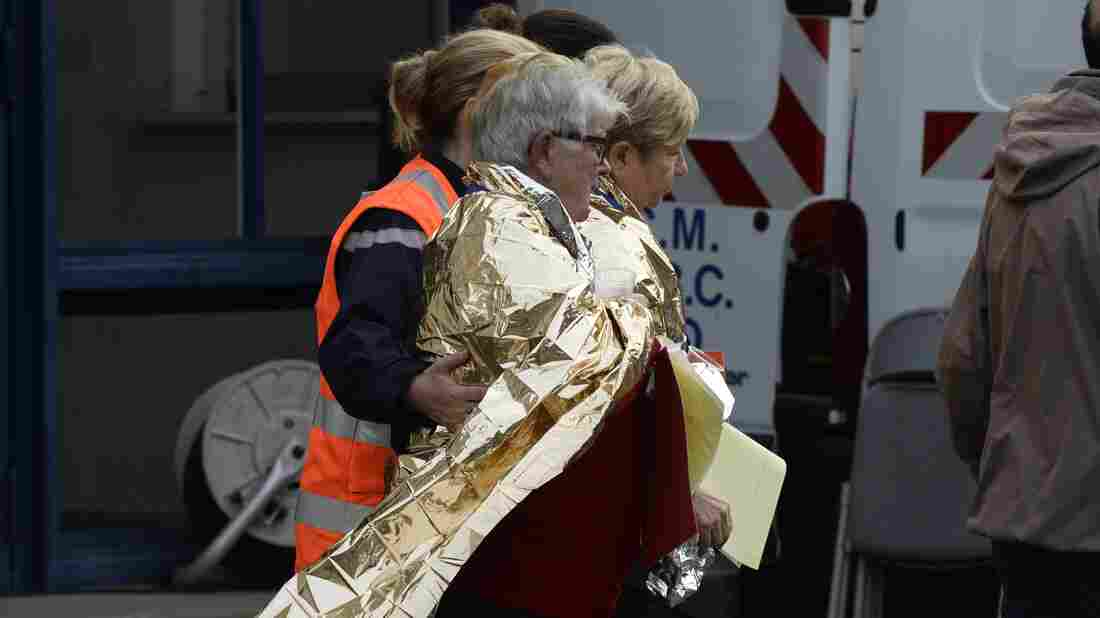 Emergency personnel escort people away from the site of a collision in Puisseguin in southwestern France. At least 40 people, most of them elderly, were killed when a bus collided with a truck  and caught fire in southwest France.