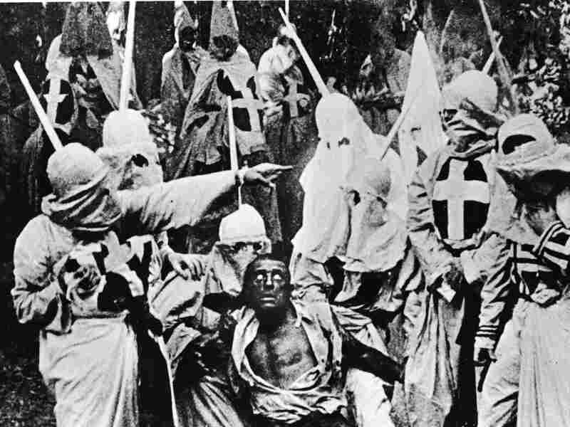 Actors in the garb of the Ku Klux Klan chase down a white actor in blackface, in a still from The Birth of a Nation.