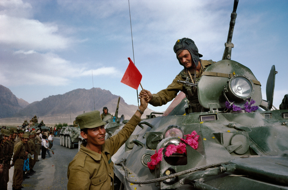 """On the first day of the Soviet withdrawal from Afghanistan in May 1988, an Afghan soldier hands a flag to a departing Soviet soldier in Kabul. """"This was the first time journalists had full access to Kabul,"""" Robert Nickelsberg says. It marked his first year covering Afghanistan. """"It was a historical turning point for the Cold War and actually foreshadows the chaos that will descend on the country."""" (Courtesy of Robert Nickelsberg/Getty Images)"""
